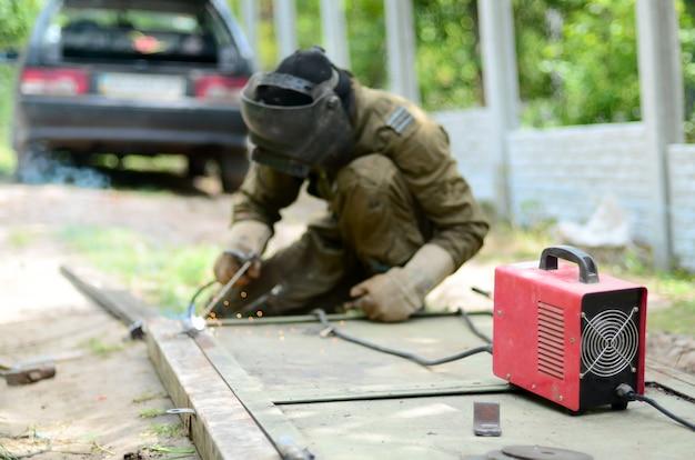 Viejo soldador en uniforme marrón, máscara de soldador y soldadores de cuero, soldaduras de puerta de metal