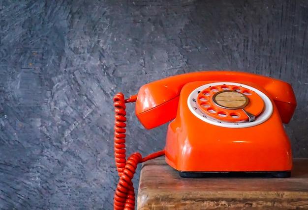 El viejo teléfono naranja suena con auricular apagado retro teléfono rotatorio sobre mesa de madera