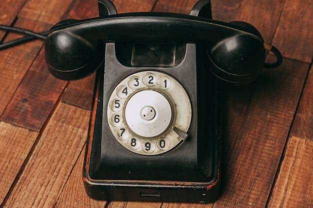 Viejo teléfono negro en el piso, vintage