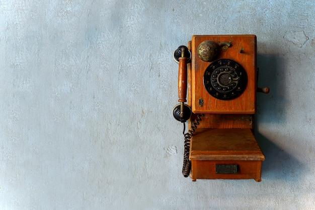 Viejo teléfono en la pared de ladrillo con luz en el fondo