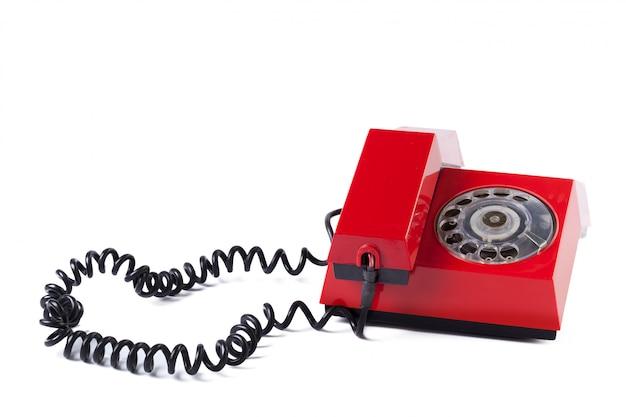 Viejo teléfono rojo sobre blanco