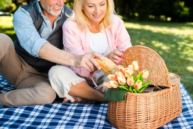 Viejo tomando pan de la cesta de picnic