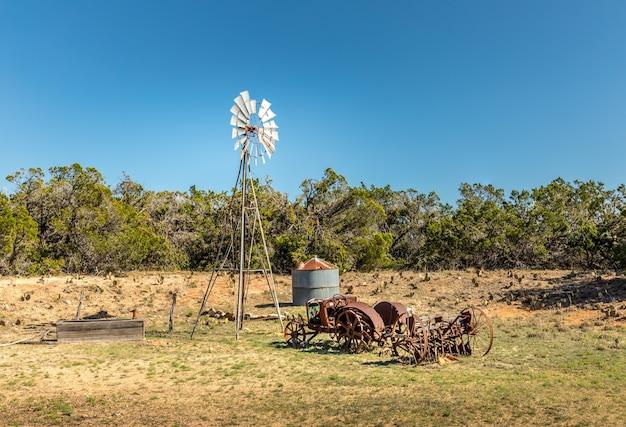 Viejo tractor oxidado y un molino de viento en las carreteras secundarias de texas