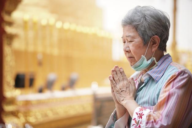 Viejo turista asiático anciano viajero mujer mayor orando en el templo budista.