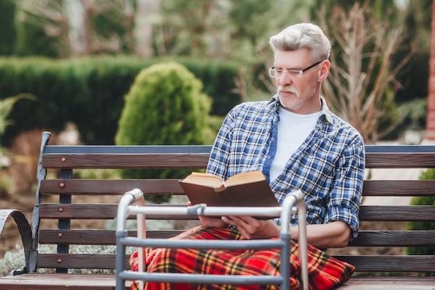 Viejo veterano leyendo un libro mientras está sentado en el jardín