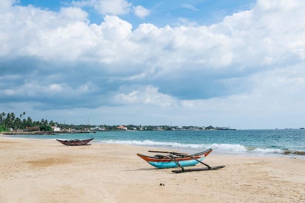 Viejos barcos catamarán en la playa contra el océano y el cielo azul con hermosas nubes en un día soleado, sri lanka