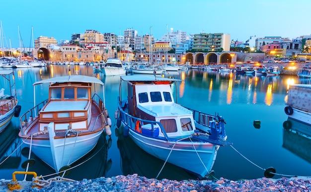 Viejos barcos de pesca en el puerto de heraklion en la noche, creta, grecia