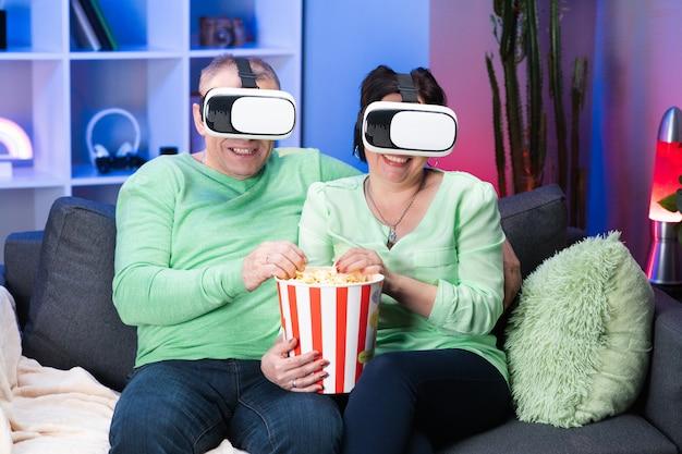 Viejos cónyuges caucásicos sentados juntos en el sofá comiendo palomitas y viendo películas en gafas de realidad virtual. familia pareja está sentada en el sofá con palomitas de maíz y viendo la televisión con gafas de realidad virtual.