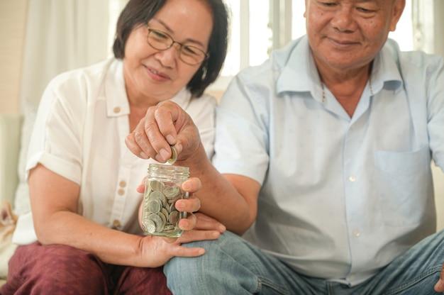 Viejos hombres y mujeres asiáticos se sientan en el sofá, hacen planes financieros.