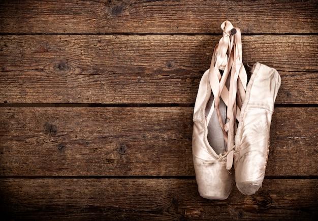 Viejos zapatos de ballet rosa usados colgando