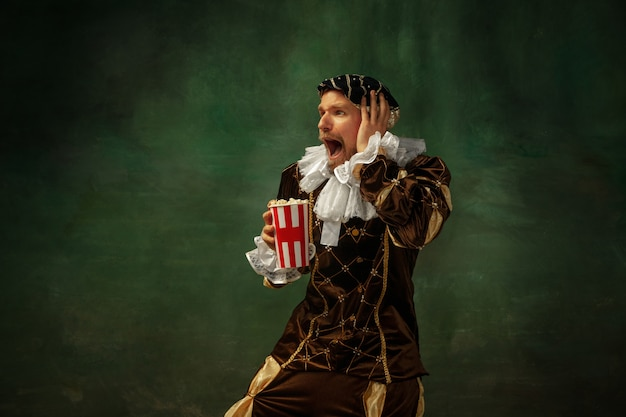 Viendo fútbol emocional. retrato de joven medieval en ropa vintage de pie sobre fondo oscuro. modelo masculino como duque, príncipe, persona de la realeza. concepto de comparación de épocas, moderno, moda.