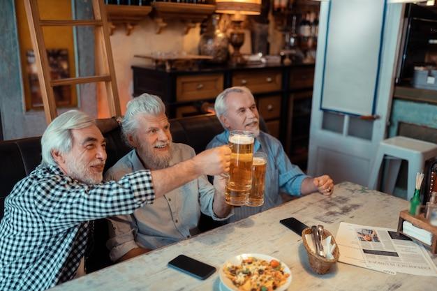 Viendo el partido de fútbol. radiante jubilados canosos viendo partido de fútbol en el pub