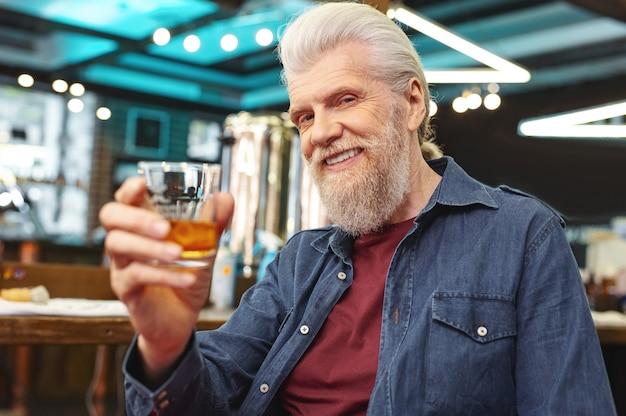 Viéndote. hombre senior encantado positivo levantando la mano con vidrio mientras posa en la cámara