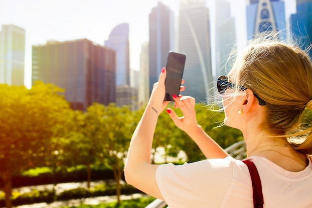 El viento sopla el pelo de la mujer mientras toma la foto de hermosos rascacielos en su iphone