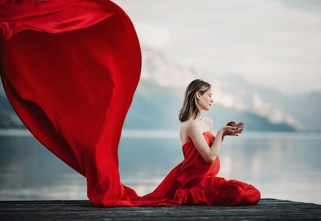 Viento sopla vestido rojo de una mujer embarazada sentada con manzana en el puente sobre el lago