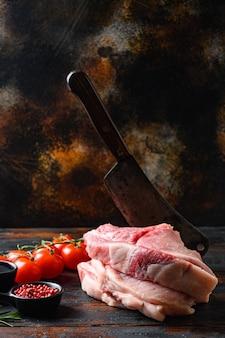 Vientre de cerdo fresco de granja, chuleta de cerdo cruda con aceite y especias para asar o cocinar en tablones oscuros de madera sobre una mesa rústica y cuchillo de carnicero, vista lateral