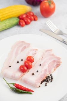 Vientre de cerdo en rodajas en un plato blanco con semillas de pimiento y tomates.