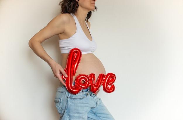 Vientre embarazado con amor globo sobre un fondo claro. copyspace