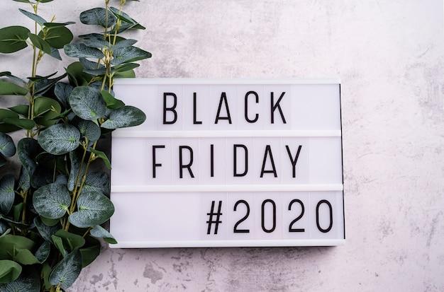 Viernes negro 2020 palabras en caja de luz con hojas de eucalipto
