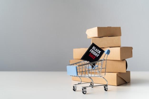 Viernes negro carrito de compras en frente de cajas