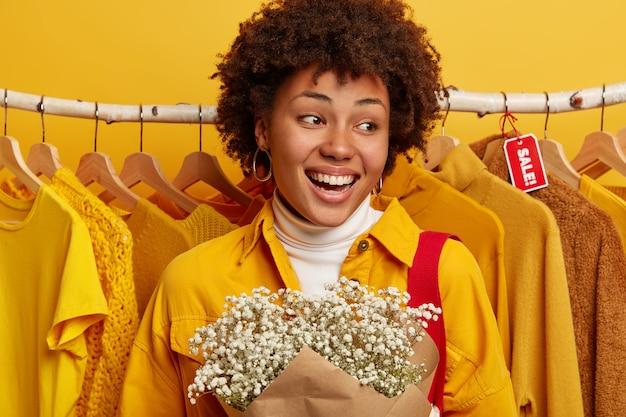 Viernes negro y concepto de reducción de precio. la mujer rizada positiva se regocija en la compra con un descuento del cincuenta por ciento de la oferta, puede comprar muchos conjuntos por poco dinero, se para cerca de la vitrina con ropa amarilla, lleva flores