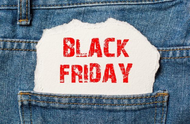 Viernes negro sobre papel blanco en el bolsillo de los pantalones vaqueros azules