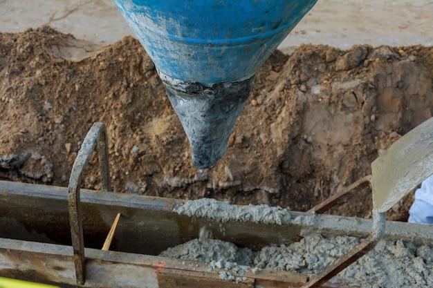 Vierta el concreto del camión de concreto, trabajadores de la construcción que vierten el concreto, enfoque selectivo