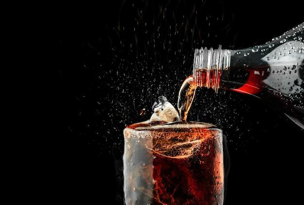 Vierta el refresco en un vaso con salpicaduras de hielo sobre fondo oscuro.