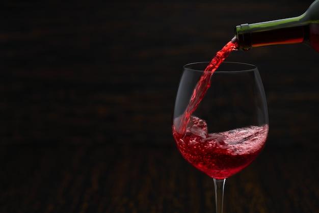 Vierta el vino tinto en un vaso sobre la mesa de madera negra, primer plano.