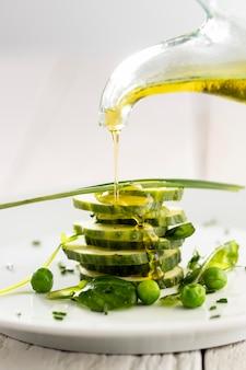 Se vierte el aceite de oliva en la ensalada de pepinos en una placa blanca.