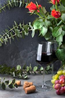 Vierte vino de una botella en un vaso, sobre un fondo negro con rosas rojas y uvas