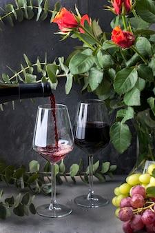 Vierte vino en un vaso sobre un fondo negro. uvas rosadas y verdes