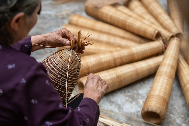 Vietnames senior es artesano haciendo la tradicional trampa para peces de bambú
