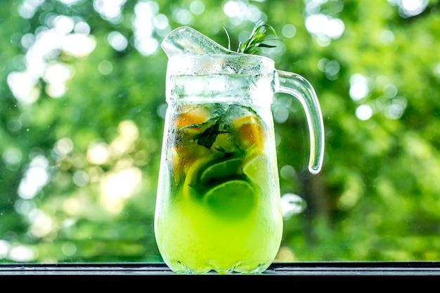 Vigorizante limonada de vista frontal en jarra con limón, lima, naranja y estragón
