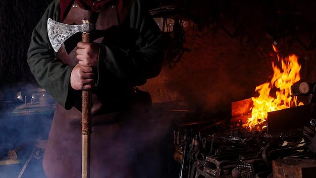 Viking forja armas y espadas en la herrería. un hombre con ropa de guerrero está en la herrería.