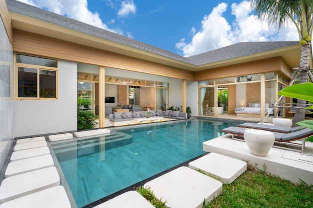 Villa de piscina tropical con jardín verde