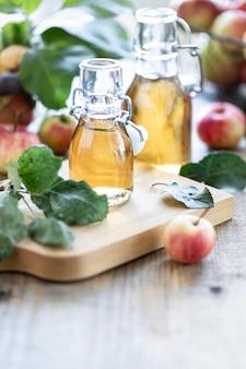 Vinagre de manzana. botella de vinagre orgánico de manzana o sidra sobre fondo de madera. comida orgánica saludable. con copia espacio.
