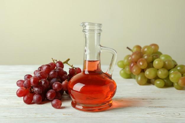 Vinagre y uva en mesa de madera blanca
