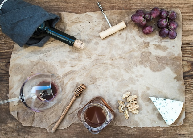 Vino y aperitivo en papel artesanal aceitoso sobre mesa de madera rústica