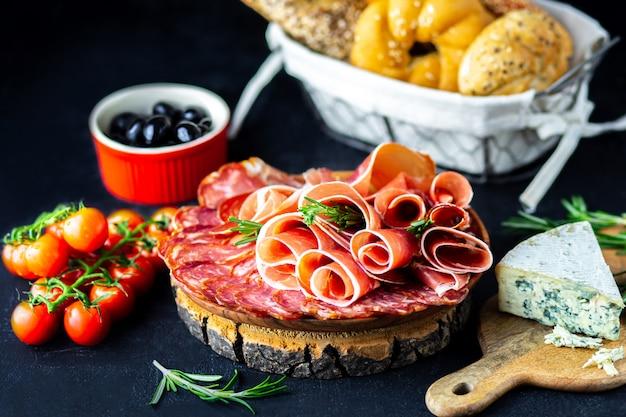 Vino aperitivo en una tabla de madera. queso blanco vino, jamón, jamón serrano, con salami y aceitunas sobre un fondo negro. pan recién horneado con queso y bocadillos de vino. sabrosos aperitivos de fiesta