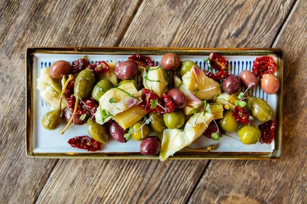 Vino aperitivos aceitunas alcachofas y tomates