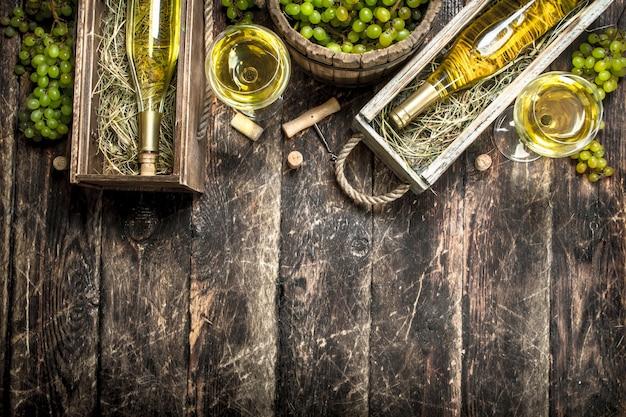 Vino blanco en cajas antiguas con uvas verdes sobre un fondo de madera