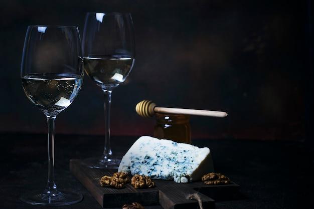 Vino blanco en copa fina con queso azul, miel, nueces en la oscuridad.