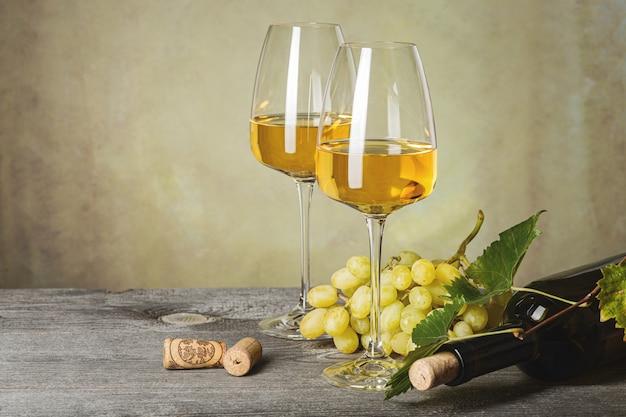 Vino blanco en copas, botella de vino y uvas en una vieja mesa de madera. fondo oscuro.