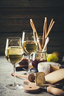 Vino blanco con surtido de embutidos en el fondo de piedra