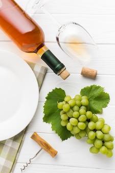Vino blanco con sus uvas.