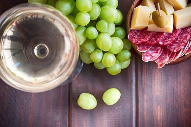 Vino blanco, uva, aceitunas y queso en la mesa de woden
