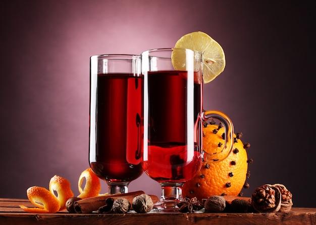 Vino caliente en las copas, especias y naranja en la mesa de madera en la pared púrpura