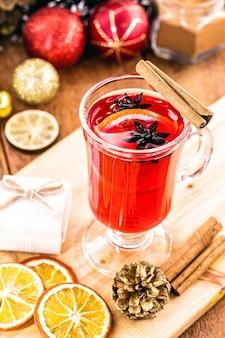 Vino caliente en copas de vidrio con especias y cítricos, mesa rústica en el fondo, tradición de fin de año