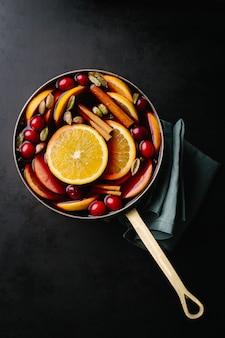 Vino caliente con frutas en una cacerola